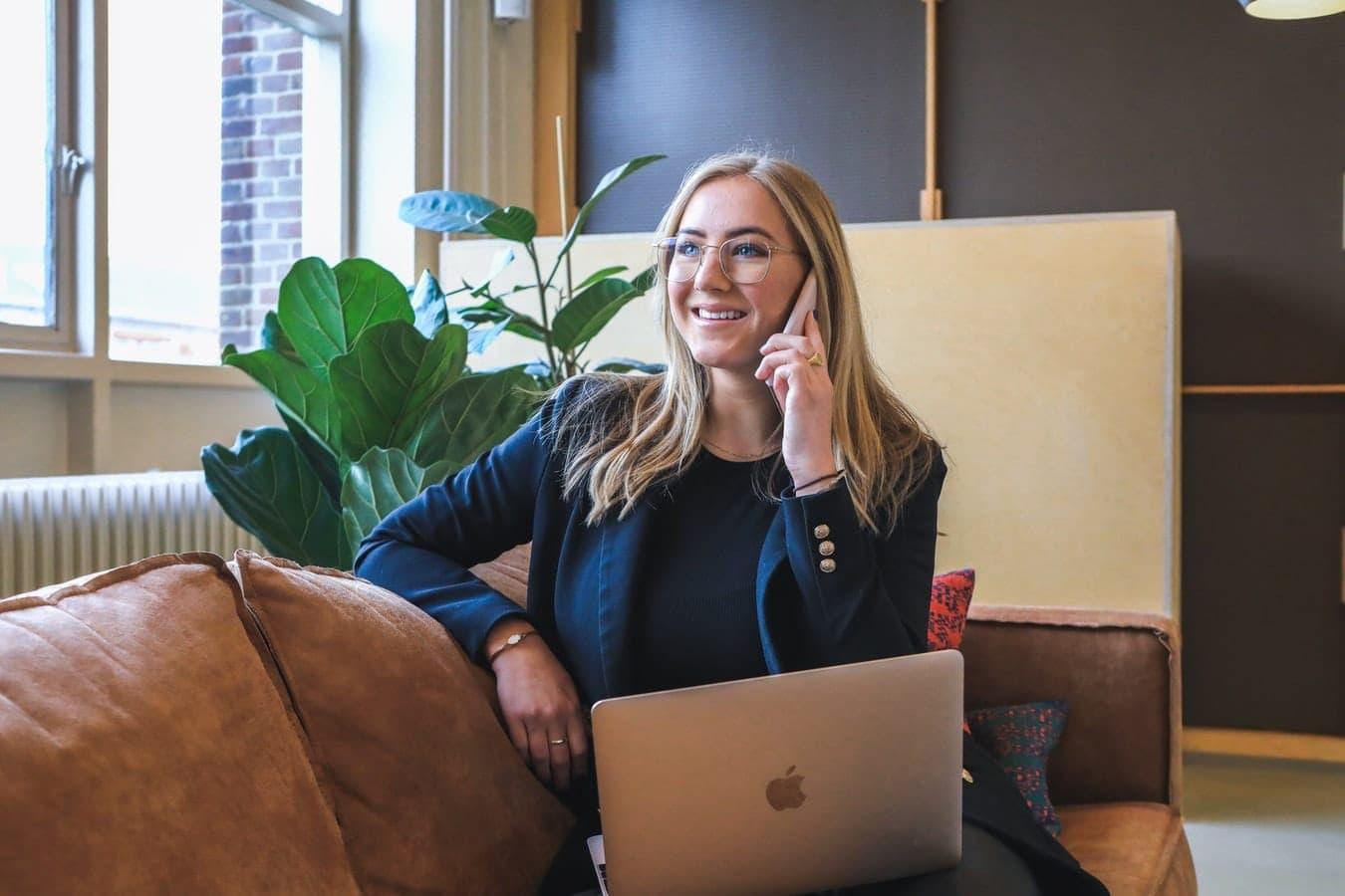 Lady smiling while on mobile call with laptop on leather sofa